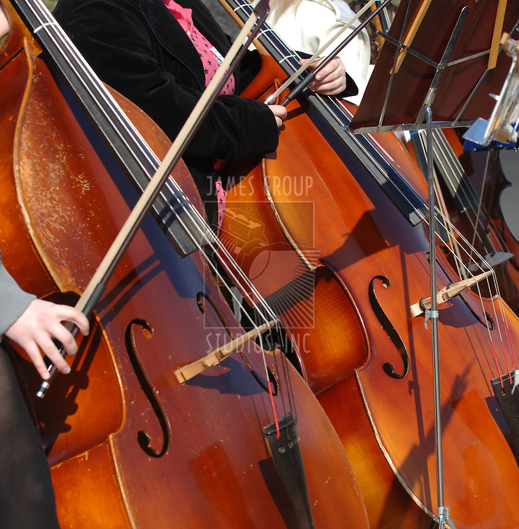 cloe-up of cellos being played in a concert