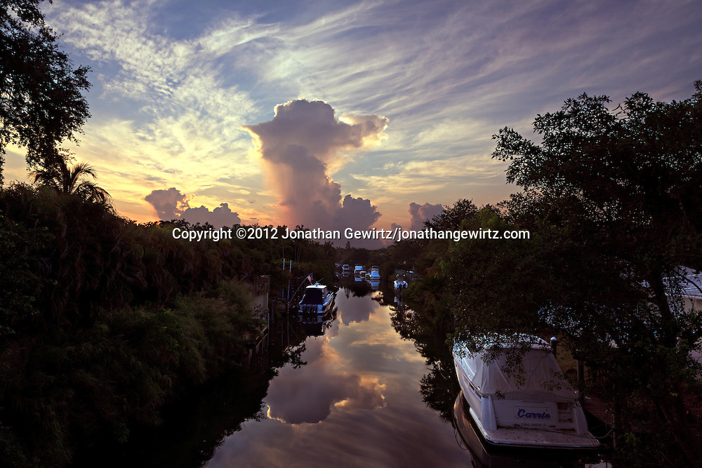 A dissipating thunderstorm reflects from the tranquil surface of a canal shortly after sunrise in Coral Gables, Florida. WATERMARKS WILL NOT APPEAR ON PRINTS OR LICENSED IMAGES.