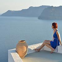 Woman in blue dress in Oia,Santorini, Kyclades,South Aegean, Greece,Europe<br /> Model release 0343