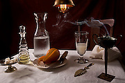 Tabletop setting. Absinthe, pear and incense.