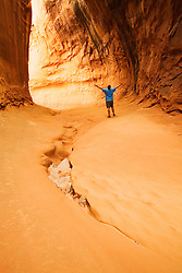 A man celebrates the beauty of nature, and the completion of his hike through a remote Utah canyon.