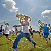 """MOC-Floyd Valley High School band members take extra long strides during a summer band camp rehearsal in August.  A normal marching step is 22 1/2 inches, or 16 steps for every 10 yards. """"If you want to be called a band geek, walk like that in the hallways at school.  You deserve whatever they call you,"""" director Steve Connell jokingly told his band.  """"But out here, that's a marching step.""""  photo by david peterson"""