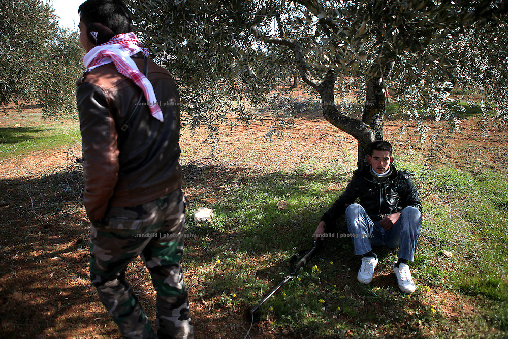 A young member of the Free Syrian Army wait hiding under a tree during a shelling of the syrian army. On 22. February the syrian army attacked the village of Kureen, Province of Idlib, Syria. Kureen was among the first villages in the northwest of Syria controlled by the opposition. Some villagers and members of the defence units escaped to surrounding olive orchards, when the attack begun in the early morning. A majority of the inhabitants didn´t manage to escape. The heavy shelling lasts 7 houres. Soldiers searched all houses, burnt some of them down, loote shops, stole cars and furniture. About 60 motorcycles were burnt down. Tanks demolished several houses. 6 men were executed. One woman died as a result of an heart attack.