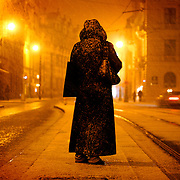 "SHOT 11/22/08 1:19:29 PM -  A Prague resident waits for the city tram as snow and sleet falls at dusk. Trip to Prague, Czech Republic with Margaret. Prague is the capital and largest city of the Czech Republic. Its official name is Hlavní m?sto Praha, meaning Prague, the Capital City. Situated on the River Vltava in central Bohemia, Prague has been the political, cultural, and economic centre of the Czech state for over 1100 years. The city proper is home to more than 1.2 million people, while its metropolitan area is estimated to have a population of over 1.9 million. Since 1992, the extensive historic centre of Prague has been included in the UNESCO list of World Heritage Sites. According to Guinness World Records, Prague Castle is the largest ancient castle in the world. Nicknames for Prague have included ""the mother of cities"", ""city of a hundred spires"" and ""the golden city"". Since the fall of the Iron Curtain, Prague has become one of Europe's (and the world's) most popular tourist destinations. It is the sixth most-visited European city after London, Paris, Rome, Madrid and Berlin. Prague suffered considerably less damage during World War II than some other major cities in the region, allowing most of its historic architecture to stay true to form. It contains one of the world's most pristine and varied collections of architecture, from Art Nouveau to Baroque, Renaissance, Cubist, Gothic, Neo-Classical and ultra-modern..(Photo by Marc Piscotty / © 2008)"