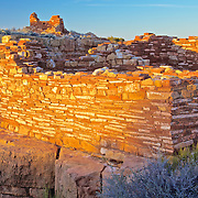 Wide-angle photo of the Lomaki Pueblo ruins with sunset reflecting off of the abode dwelling located in Wupatki National Monument outside of Flagstaff, Arizona taken by Leandra Melgreen Lewis.