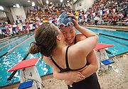 Hartley's Andrea Cottrell gets a hug from Academy's India Sherman after winning the 100-yard breaststroke during finals of the Div. II state swim meet at CT Branin Natatorium in Canton on Feb. 24, 2012.