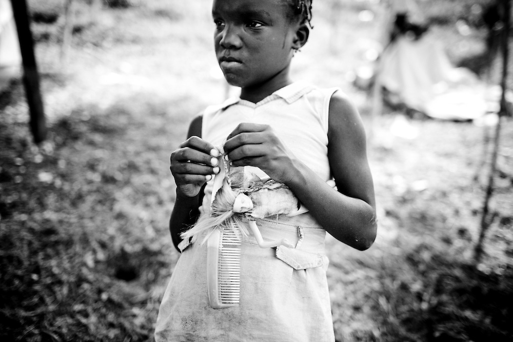 A girl plays with her doll in a camp for those displaced by the recent earthquake in Petionville, outside Port-au-Prince, Haiti.