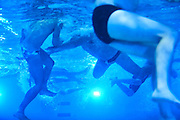 A view from below of Seattle Otters Water Polo players during a scrimmage at Medgar Evers Pool. Treading water is crucial in a sport with seven-minute quarters of constant swimming. (Benjamin Benschneider/The Seattle Times)