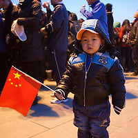 China, Beijing, Young boy holds Chinese flag while waiting for sunrise flag raising ceremony in Tiananmen Square on cold spring morning