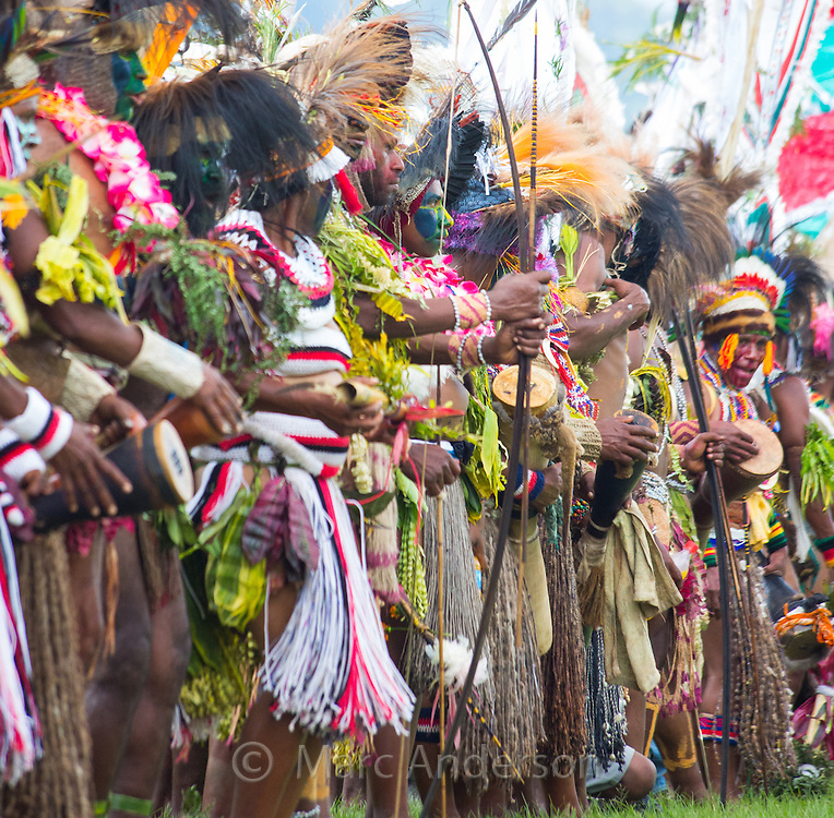Men and women from various tribes standing together in traditional dress at the Goroka show in the highlands of Papua New Guinea.