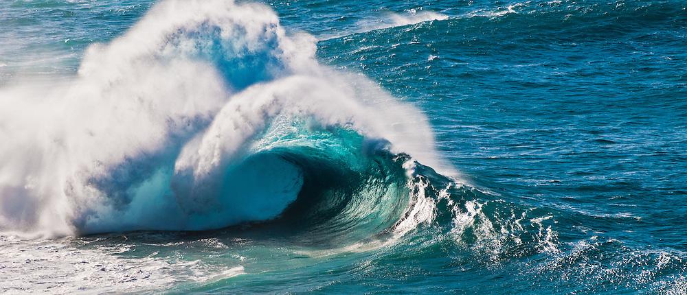 Wave breaking off the Na Pali coast of Kauai, Hawaii