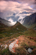 Taken on a evening at the end of August, one hour before sunset, looking down to the valley from the Col dell'Agnello, a pass at more than 2700 m. linking Italy to France. This is the Val Varaita, one of the many valleys in the Italian side of the Western Alps in Piedmont. It had been cloudy, with dull light, for most of the day. However, a few minutes before sunset the sun broke through the storm tinging the clouds and the peaks with beautiful pinks. There was quite a strong wind down in the valley, so I decided for a very long exposure just to capture the beautiful movement of the fog in the middle ground and the clouds in the foreground.