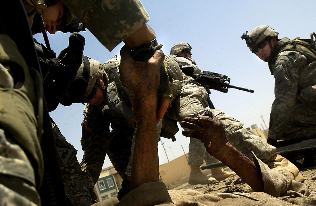 August 10, 2006: SSG Eric Forbes holds the hand of an injured Iraqi man lying in the street after a suicide car bomb explosion at an intersection in Tameem, Ramadi, Iraq while medic SPC John Schroeder treats him. The soldiers from Bravo Company 2-6 Infantry, Task Force 1-35 from Baumholder GE, were performing a routine patrol at an intersection in Tameem, a suburb of Ar Ramadi when a suicide car bomb exploded about twenty five meters in front of the patrol. Initial reports indicate that 2 were killed (1 civilian and the bomber) and 4 were wounded (1 Iraqi Police Officer and 3 civilians). Immediately after the explosion, Soldiers of Bravo Company cordoned off the area, treated and evacuated the wounded and maintained security until an Explosive Ordinance Disposal team (EOD) arrived to clear the area.  One civilian died of wounds at the treatment facility.  While EOD was on scene, the patrol took small arms fire from outside of the cordon.  EOD recovered one 110mm artillery round and three 115mm rounds that were believed to be connected with detonation wires from the dashboard of the vehicle. The mission is part of the continuing support of the 1-1 Armored Division.  1-1AD is deployed with I Marine Expeditionary Force (Forward) in support of Operation Iraqi Freedom in the Al Anbar province of Iraq (Multi National Forces-West) to develop the Iraqi security forces, facilitate the development of official rule of law through democratic government reforms, and continue the development of a market based economy centered on Iraqi reconstruction. (U.S. Air Force photo by Tech Sergeant Jeremy T. Lock) (Released) — © TSgt Jeremy Lock/