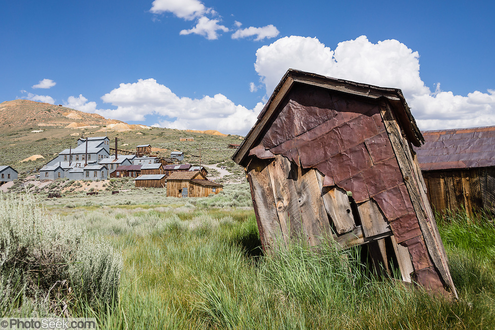 """Dilapidated outhouse near the Standard Stamp Mill at Bodie gold mining ghost town 1859-1942, California, USA. Bodie State Historic Park lies in the Bodie Hills east of the Sierra Nevada mountain range in Mono County, near Bridgeport. After W. S. Bodey's original gold discovery in 1859, profitable gold ore discoveries in 1876 and 1878 transformed """"Bodie"""" from an isolated mining camp to a Wild West boomtown. By 1879, Bodie had a population of 5000-7000 people with 2000 buildings. At its peak, 65 saloons lined Main Street, which was a mile long. Bodie declined rapidly 1912-1917 and the last mine closed in 1942. Bodie became a National Historic Landmark in 1961 and Bodie State Historic Park in 1962."""