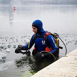 Entra&icirc;nement des plongeurs Gendarmerie de la Brigade Fluviale de Conflans dans un lac gel&eacute;. Les temp&eacute;ratures ext&eacute;rieures sont bien en dessous de z&eacute;ro depuis plusieurs jours mais cela n'emp&ecirc;che pas ces gendarmes de poursuivre leur entra&icirc;nement. Ils brisent l'importante &eacute;paisseur de glace de l'etang pour se mettre &agrave; l'eau puis r&eacute;alisent leur plong&eacute;e en surface non libre, assur&eacute;s par une corde attach&eacute;e au ponton et sous la surveillance de coll&egrave;gues rest&eacute;s en surface. <br /> Janvier 2017 / Conflans Sainte Honorine (78) / FRANCE<br /> Voir le reportage complet (40 photos) http://sandrachenugodefroy.photoshelter.com/gallery/2017-01-Plongee-sous-glace-en-Gendarmerie-Complet/G0000dbiIWNVaY1s/C0000yuz5WpdBLSQ
