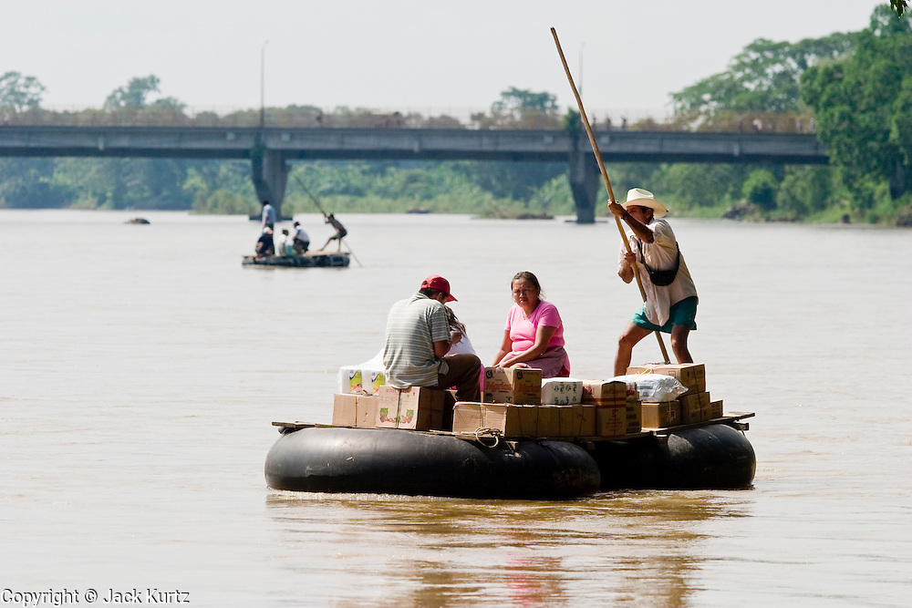 07 OCTOBER 2003 -- TAPACHULA, CHIAPAS, MEXICO:  People from Guatemala ride on rafts across the Rio Suchiate towards the Mexican town of Hidalgo, near Tapachula. Tapachula is center of the smuggling industry between Mexico and Guatemala. Consumer goods are smuggled south to Guatemala (to avoid paying Guatemalan import duties) and people are smuggled north into Mexico. Most of the people coming north are hoping to eventually get to the United States.  PHOTO BY JACK KURTZ