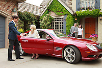 A couple in a red Mercedes Benz arriving at their friends home