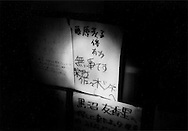 Notice for missing persons is illuminated by flash light (torch) because there is no electricity at this evacuation shelter (a middle school), except limited spaces powered by generator, and even there, fuel is in very short supply.  Otsuchi, Iwate Prefecture, Japan.  There are over 26,000 people either missing or dead and the current death toll has risen above 10,000 people.
