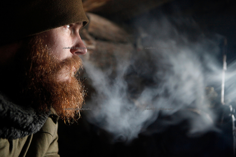 Craig smokes a cigarette in a frontline position near Donetsk.<br /> <br /> +++   +++ The Boom Stick Brotherhood +++   +++  <br /> <br /> Driven by a certain fascination on military and a simple shaped nationalistic ideology young men travel the world to fight at frontlines of recent conflicts. Five volunteering warriors from europe and the US were walking into battle in Ukraine last year. Ben, Alex, Craig, Charlie and Cowboy made it to the frontline joining the right-wing militia Right Sector (Prawji Sektor) to defend Ukraine by fighting seperatists and russian irregular forces aiming to split off the eastern Donbass region from the country.<br /> <br /> As ukrainian forces are short of servicemen Right Sector is welcomed to support the defense efforts at hotspots. Receiving no payments but shelter, food and ammonition the foreigners selfmade battlegroup Task Force Pluto found itself in a so called Anti-Terror-Operation close to the Donetsk Airport. Though Minsk II Agreement for Ceasefire is in effect several daily fire exchanges taking place between both conflict parties at the line of contact. However the war is now fought in a World War I alike stalemate in muddy trenches which were digged during the World War II.<br /> <br /> As a loose union of individuals the Boom Stick Brotherhood is no certain ukrainian phenomenon and not tied to the recent war only. If things would become boring, crazy or if the army leadership would deter foreigners from fighting Ben and his comrades would move on looking for another destination around the globe to be involved in battle. That&acute;s what they are aiming for. They are living a dream of smoking guns, camaraderie and a simple outdoor life. A lifestyle devoted to look every day into the ugly face of death.<br /> <br /> The Boom Stick Brotherhood is a multi-national, multi-religious and multi-ethnic group of men in its twenties:<br /> Ben, an austrian infantryman travelling to hot zones since years. Bored and frustrated by hi