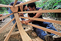 Inupiat boat builders attach wood ribs of an Iñupiaq skin whaling boat by Leonard Apangalook Sr., Gambell, Alaska.  This boat was built during the Ttraditional Native Boat Project at the Alaska Native Heritage Center, Anchorage