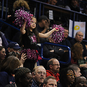 A young cheerleader cheers on the women's basketball team from the stands. (Photo by Rajah Bose)
