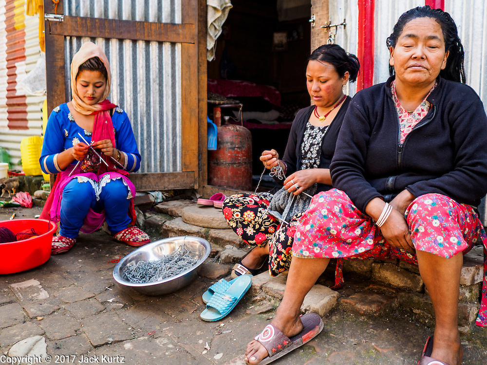 03 MARCH 2017 - BHAKTAPUR, NEPAL: Women sit in front of their temporary shelters in an informal IDP center in Bhaktapur. Bhaktapur, a popular tourist destination and one of the most historic cities in Nepal was one of the hardest hit cities in the earthquake. Recovery seems to have barely begun nearly two years after the earthquake of 25 April 2015 that devastated Nepal. In some villages in the Kathmandu valley workers are working by hand to remove ruble and dig out destroyed buildings. About 9,000 people were killed and another 22,000 injured by the earthquake. The epicenter of the earthquake was east of the Gorka district.      PHOTO BY JACK KURTZ