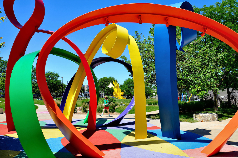 Little Girl Walking in Park Beside Colorful Abstract Art in Omaha, Nebraska<br /> Near the Joslyn Memorial Art Museum in Omaha, Nebraska, is a playground featuring large abstract sculptures. Children are drawn towards the vibrant colors and then stay for the fun they provide.