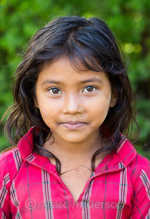 Beautiful young Tharu girl wearing a traditional cotton shirt in the Terai region in Nepal