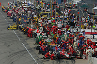 The teams pit during a caution period at the Chicagoland Speedway, September 11, 2005