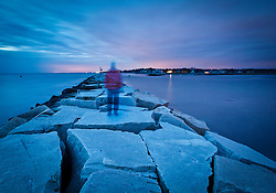 Ghost-like image of a man on the breakwater in Rye Harbor State Park, Rye, New Hampshire.