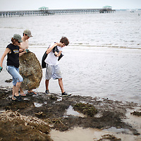A mother and two of her sons remove debris from the beach in a coast-wide cleanup effort at Bay St. Louis, Mississippi May 8, 2010.  Citizens all along the Gulf of Mexico were asked to remove debris that could hinder efforts to clean up the BP oil spill if it reaches the shore.  L-R are Judith McCall, Dawson McCall and Jonas Powers.   REUTERS/Rick Wilking (UNITED STATES)