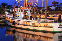 Old Pilgrim fishing trawler lit by a street light at twilight in Wancheese Harbor, Outer Banks.