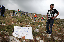 Palestinian refugees further up the mountain, look on as others protest at the border fence in the valley below.