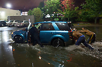 Good Samaritans help push a car out of flood waters on Washington Street and into a nearby Burger King parking lot in Worcester, Massachusetts on October 21, 2016.  Flash flooding in the area left many motorists stranded and closed down parts of route I-290.  Copyright Matthew Healey<br /> <br /> (FREELANCE SUBMISSION)