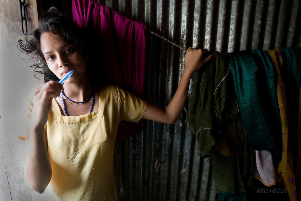 Sex worker Shetu, 17, brushes her teeth at brothel in Tangail, Bangladesh.
