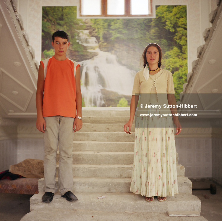 Roma youths stand on the stairs of their house which is still under construction. A photo-mural of a forest scene decorates the half way landing of their stairs. These photo-posters are now replacing hand painted murals within the Roma homes as the favoured wall decorations.