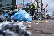 Een medewerker van handhaving bekijkt de vuilnis op straat. in de Utrechtse binnenstad begint de staking bij de vuilophaaldiensten langzaam zichtbaar te worden. De prullenbakken raken overvol en vogels vreten aan de vuilniszakken. Toch valt de overlast nog mee, mede dankzij de lage temperaturen en omdat veel bedrijven en mensen hun vuil binnenshuis houden.  De medewerkers van de gemeentereiniging laten zo hun onvrede blijken dat na een jaar onderhandelen nog steeds geen CAO is afgesloten.<br /> <br /> In Amsterdam, Utrecht and Groningen, the garbage is not collected. The employees of the municipal sanitation show their grieves since after a year of negotiations still no collective agreement has been concluded.