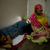 Dai Tara proudly hold Sadef's second baby which she helped deliver an hour ago in her own home.<br /> She loves bringing new life into the world and loves the fact that the community respects her for the work she does.<br /> Karachi, Pakistan, 2011