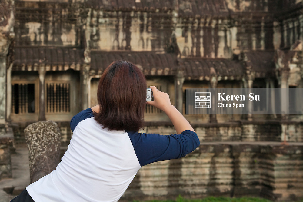 Tourist photographing at Angkor Wat, UNESCO World Heritage site.