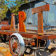 An antique vehicle with the word ART sits along the highway in Sisterdale, Texas.