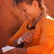Portrait of climber Kitty Calhoun taping up in preparation to climb at Maverick Buttress, near Moab Utah.