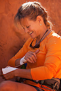 Portrait of climber Kitty Calhoun taping up in preparation to climb at Maverick Buttress, near Moab Utah.