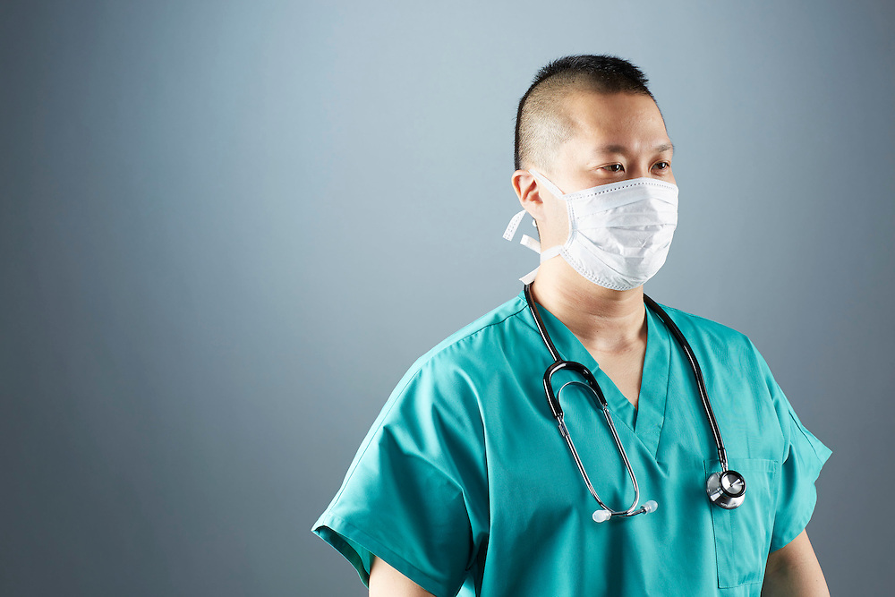 A portrait series representing the intense emotions that Doctors face.  An Asian male Doctor wearing a white surgical mask, stethoscope, and green medical scrub suit shown.