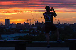 Primrose Hill, London, September 27th 2016. A man takes a picture of the city's skyline from Primrose Hill as dawn breaks over London. &copy;Paul Davey<br /> FOR LICENCING CONTACT: Paul Davey +44 (0) 7966 016 296 paul@pauldaveycreative.co.uk