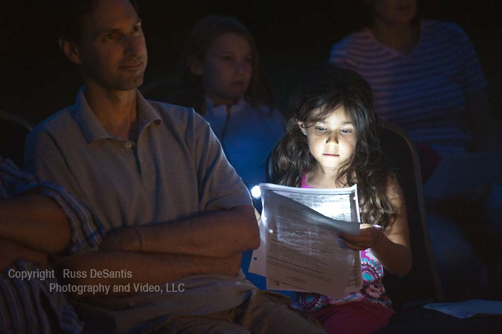 Mia Dasaro, 6, is lit by the light of her flashlight as she follows along during a program about the shofar held at the Monmouth Reform Temple in Tinton Falls.  At left is her father Dan Dasaro of Holmdel. In the background, (visible between Dan and Mia), is Amy Leifman of Red Bank. - 8/30/11 / Photo by Russ DeSantis for NJJN