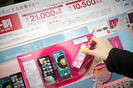 A consumer looks over the Docomo handset in Tokyo, Japan February 2, 2009. NTT DoCoMo Inc., Japan's top mobile phone carrier, said Friday, Jan. 30, 2009, its net profit for the April-December period grew 16 percent from a year earlier, benefiting from a new installment-based system for selling handsets and a slowdown in the number of subscribers jumping ship to rivals.