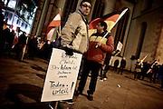 Frankfurt am Main | 09 Feb 2015<br /> <br /> Am Montag (09.02.2015) demonstrierte bereits zum dritten Mal die islamfeindliche und rassistische Gruppierung PEGIDA (Patrioden gegen die Islamisierung des Abendlandes) unter F&uuml;hrung der Frankfurterin Heidi Mund und in Gegenwart des Neonazis und Vorsitzenden der NPD Hessen, Stefan Jagsch, an der Katharinenkirche in Frankfurt am Main, PEGIDA konnte etwa 100 Demonstranten mobilisieren. An den Gegendemos nahmen etwa 1000 Menschen teil.<br /> Hier: Ein PEGIDA-Aktivist mit einem Transparent mit der Aufschrift &quot;Ich wurde Christ. Der Islam ist zu Hause mein Todesurteil!&quot;.<br /> <br /> &copy;peter-juelich.com<br /> <br /> [No Model Release | No Property Release]