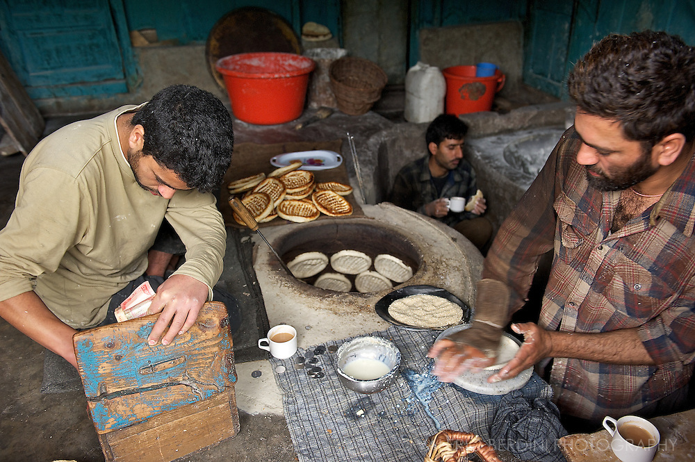 A Bakery at work. A man prepares bread, one is at the till and another has breakfast. Bread in Srinagar is cooked on the walls of traditional wood-fire ovens. Kashmir. India