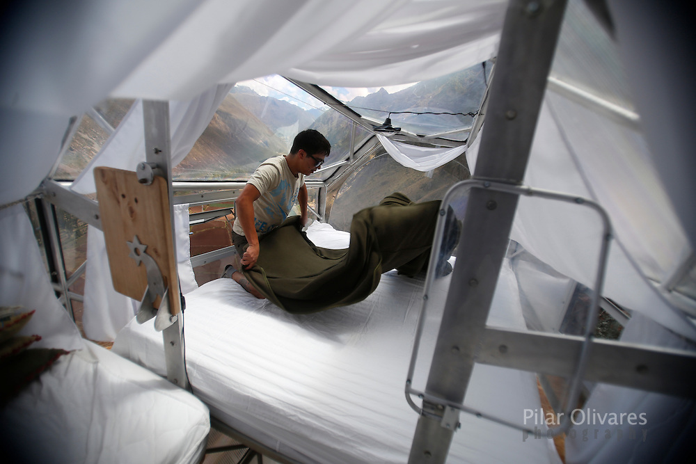 """A guide cleans a sleeping pod at the Skylodge Adventure Suites in the Sacred Valley in Cuzco, Peru, August 14, 2015. Tourists taking on an arduous climb up the steep cliff face of Peru's Sacred Valley are being rewarded for their efforts by being able to spend the night in transparent mountaintop sleeping pods at the """"Skylodge Adventure Suites"""". To reach the pods, visitors need to climb 400 metres of via ferrata (a steel cable and rungs) up the valley side or hike an intrepid trail through zip lines. REUTERS/Pilar Olivares"""