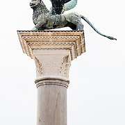"A statue of the winged Lion of St. Mark, one of two patron saints of Venice, rises on a tall granite column erected in the 1200s in Piazzetta San Marco, in Venice, Veneto, Italy, Europe. The winged Lion of St. Mark, which appeared on the flag and coat of arms of the Republic of Venice, is still featured in the red-yellow flag of the city of Venice (with six tails, one for each sestiere of the city), in its coat of arms, and in the yellow-red-blue flag of the Veneto region (which has seven tails representing its seven provinces). The winged lion also appears in the naval ensign of the Italian Republic, alongside the coat of arms of three other medieval Italian maritime republics (Genoa, Pisa and Amalfi), as well as the Golden Lion, awarded at the Venice Film Festival. Venezia is the capital of Italy's Veneto region, named for the ancient Veneti people from the 900s BC. The romantic ""City of Canals"" stretches across 100+ small islands in the marshy Venetian Lagoon along the Adriatic Sea between the mouths of the Po and Piave Rivers. The Republic of Venice was a major maritime power during the Middle Ages and Renaissance, a staging area for the Crusades, and a major center of art and commerce (silk, grain and spice trade) from the 1200s to 1600s. The wealthy legacy of Venice stands today in a rich architecture combining Gothic, Byzantine, and Arab styles."